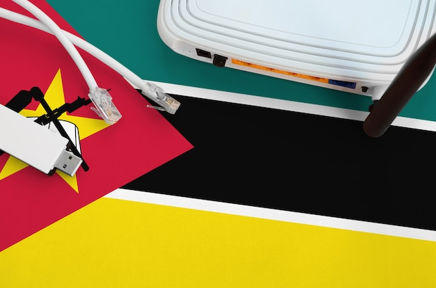 Флаг мозамбика изображен на столе с помощью интернет-кабеля rj45, беспроводного usb-адаптера wi-fi и маршрутизатора. концепция интернет-связи