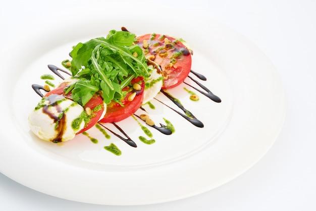 Сыр моцарелла, помидоры, руккола и соус песто в белой тарелке.