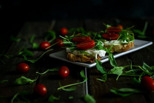 Mozzarella, arugula and cherry tomatoes bruschetta on a rustic table