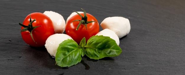 Сыр моцарелла, базилик и помидоры черри на шиферной каменной доске, копией пространства. ингредиенты для салата капрезе