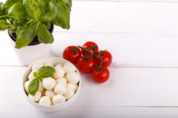 Mozzarella cheese, basil and tomato cherry balsamic white wooden board copy space. ingredients for caprese salad