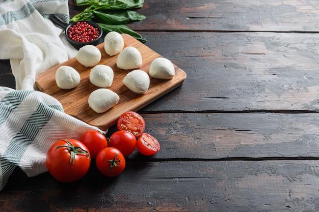 모짜렐라 치즈, 오래된 나무 배경 테이블 위에 있는 바질 토마토 체리, 텍스트를 위한 선택적 포커스 공간.