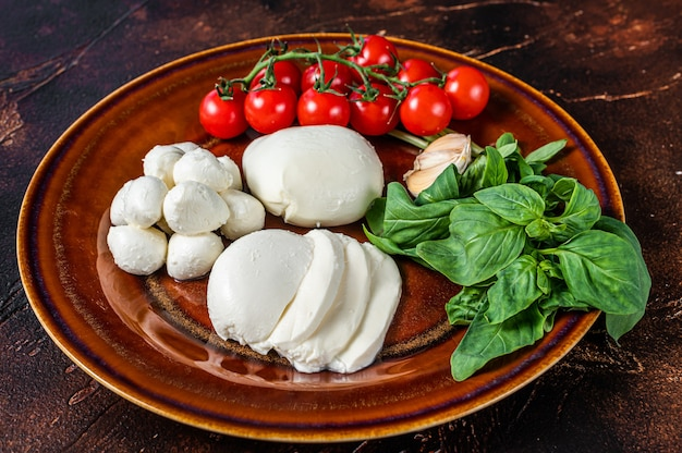 Mozzarella cheese, basil and tomato cherry ready for cooking caprese salad. dark background. top view.
