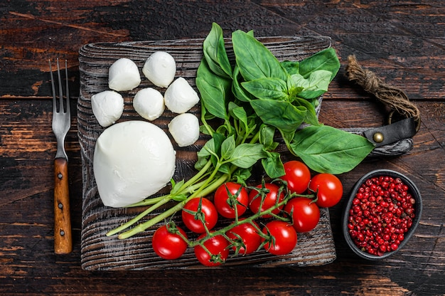 Mozzarella cheese, basil and tomato cherry on wooden board, ingredients for caprese salad. dark wooden background. top view.