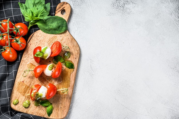 Mozzarella cheese canape sandwiches on skewers, caprese salad. gray background. top view. copy space