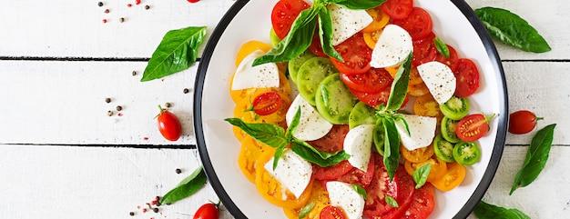 Сыр моцарелла, помидоры и базилик листья травы в тарелку на белый деревянный стол. салат капрезе. итальянская еда. баннер. вид сверху