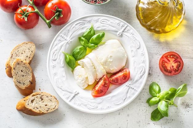 모짜렐라 치즈 토마토 바질과 올리브 오일. 카프레제 샐러드 - 이탈리아식 또는 지중해식 식사 또는 전채. 상위 뷰입니다.
