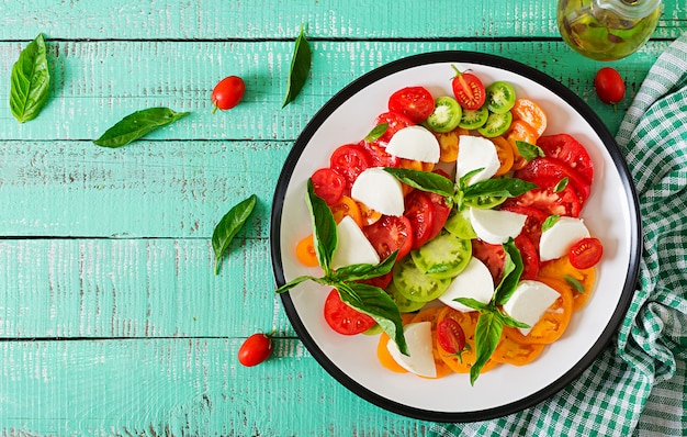 Mozzarella cheese, tomatoes and basil herb leaves in plate on the white wooden table