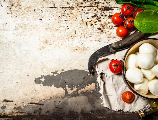 Сыр моцарелла, помидоры, оливковое масло и старый нож.
