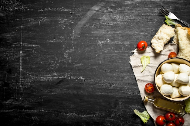 Mozzarella cheese, tomatoes, olive oil and herbs on an old fabric on a black wooden background