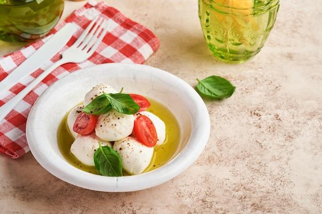 白いセラミック プレートとトマト チェリーにバジルとチェリー トマトのモッツァレラ チーズ