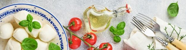 白いセラミックプレートにバジル、トマトチェリーオリーブオイルとスパイスグラインダー、調味料、スレート石の背景にペッパートマトチェリーとモッツァレラチーズ。モックアップ。カプレーゼサラダの材料。