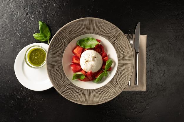 Сыр моцарелла со свежими помидорами и салатом из базилика. подается с соусом песто. блюдо с овощами для меню ресторана подается со столовыми приборами на черном каменном столе