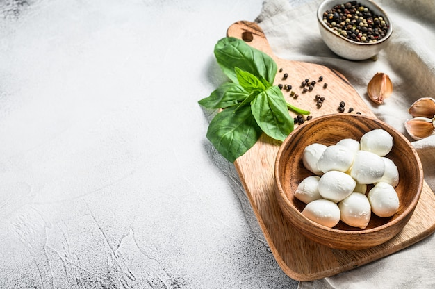 Mozzarella cheese in a wooden bowl with basil leaves. gray background. top view. copy space