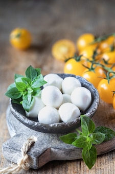 Mozzarella cheese, yellow tomatoes and basil in a ceramic bowl on a wooden board. caprese salad ingredients. selective focus