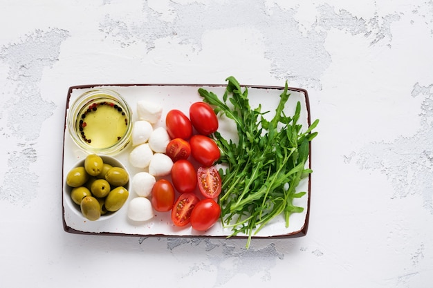 모짜렐라, 체리 토마토 및 arugula는 회색 질감 위에 올리브 오일과 함께 흰색 세라믹 직사각형 접시에 제공됩니다.