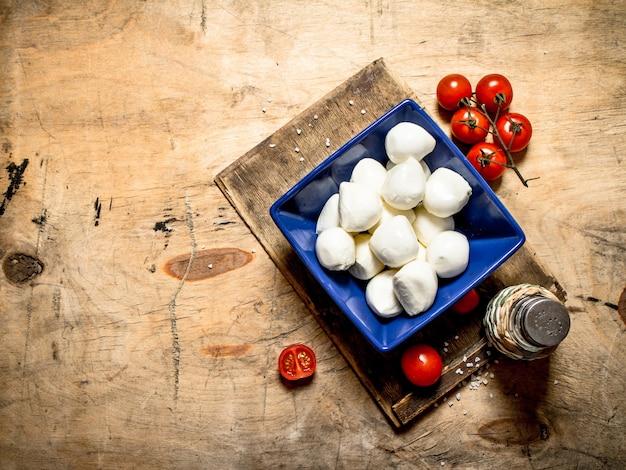 Моцарелла в миске с солью и помидорами.