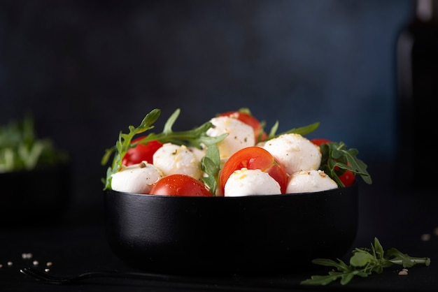 Mozzarella salad of cherry tomatoes and arugula seasoned with olive oil in a black bowl, close up