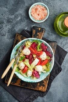 モッツァレラ、トマト、新鮮なサラダの葉のミックス、暗い背景