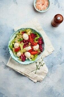 모짜렐라, 토마토 및 신선한 샐러드 잎, 슬레이트 돌 테이블 배경, 평면도의 혼합. 모의.