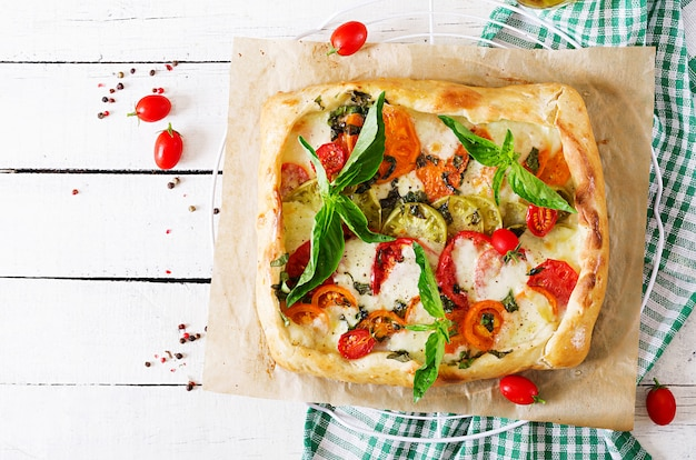 Mozzarella, tomatoes, basil savory pie on a white wooden table. delicious food, appetizer in a mediterranean style. top view. flat lay