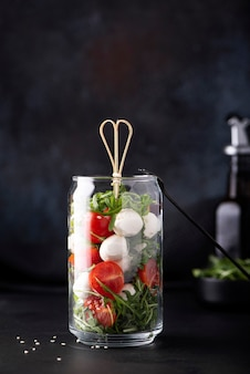 Mozzarella with cherry tomatoes and arugula in a glass jar on a dark background