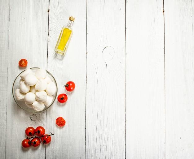 Моцарелла с помидорами и оливковым маслом на белом деревянном фоне