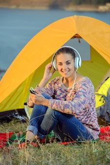 若い女性がテントの中でmp3プレーヤーを聴きます。