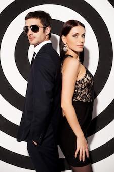 夫婦...背中合わせに、黒と白の背景に立っている美しい若い身なりのよいカップル