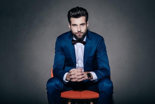 自信さん。灰色の背景にオレンジ色の椅子に座ってカメラを見てスーツと蝶ネクタイの若いハンサムな男