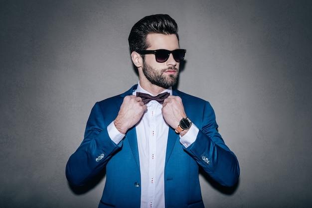パーフェクトさん。サングラスをかけて蝶ネクタイを調整し、灰色の背景に立って目をそらしているハンサムな若い男のクローズアップ