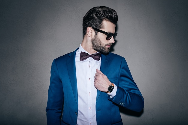 パーフェクトさん。彼のジャケットを調整し、灰色の背景に立っている間彼の肩越しに見ているサングラスを身に着けているハンサムな若い男のクローズアップ