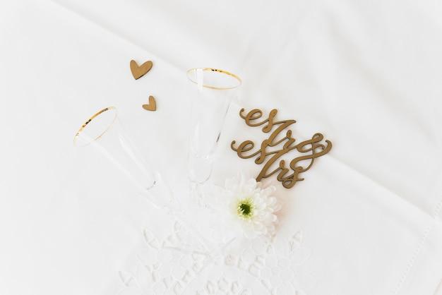 結婚式の言葉mrと花を持つ夫人。白い背景の上のガラスとハートの形を飲む