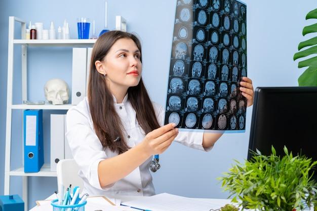 女性医師が彼女のオフィスで患者のmr画像を調べる