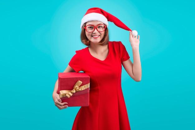 Миссис санта. красивая молодая азиатская женщина в шляпе санта, держа подарок изолированный на синем.
