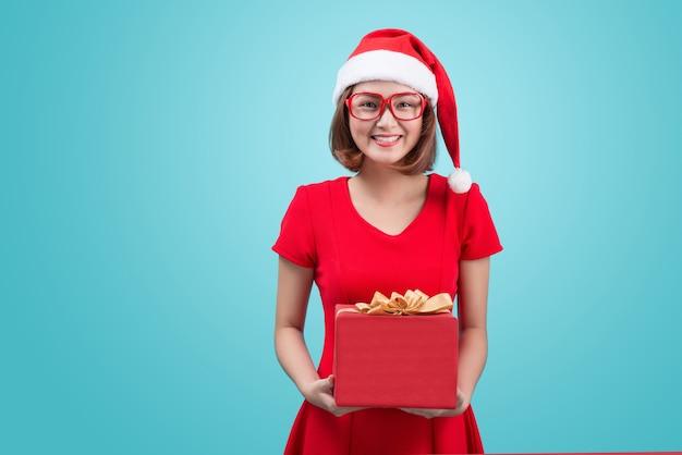 サンタ夫人。青で隔離の贈り物を保持しているサンタの帽子の美しい若いアジアの女性。