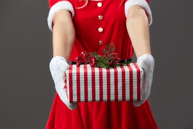 Мисс санта-клаус, одетая в красный халат и белые перчатки, держит в руках рождественский подарок на сером фоне. .
