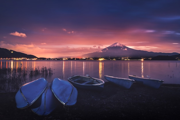 Mt. fuji over lake kawaguchiko with boats at sunset in fujikawaguchiko, japan.