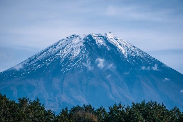 Mt. фудзи на предпосылке голубого неба с листвой осени на дневном времени в fujikawaguchiko, японии.