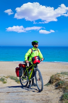 Mtb biker bicycle touring on a beach with pannier