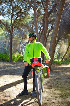 Mtb biker bicycle touring in a pine forest