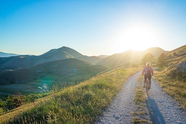イタリア、アペニン山脈、グランサッソのアブルッツォ地方の山岳地帯にあるmtb。緑の風景のユニークな山の風景の太陽バーストバックライトでサイクリングする女性。夏の野外活動。