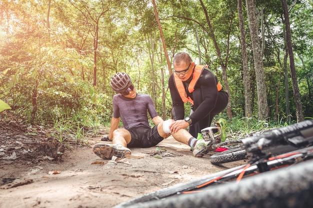 Mtbマウンテンバイクの事故と応急処置:バイカーの衝突事故、膝と脚の負傷、マウンテンバイクの事故を助けるための応急処置。マウンテンバイクアスリートの応急処置チームがレース事故で負傷しました。
