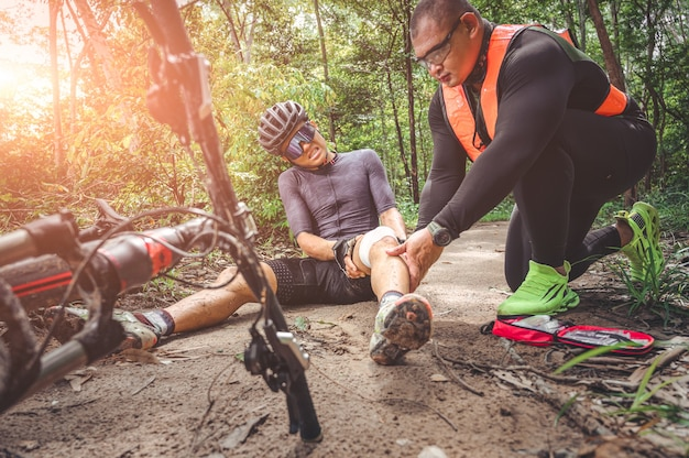 Mtb mountain bike accident and first aid : biker crash crashes, injuring knee and leg, first aid to help mountain biker in accident. mountain bike athlete first aid team injured during race accident.
