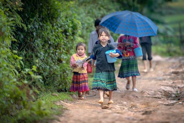 女の子が自宅の近くの田舎道で米のパッケージを運んでいます。ベトナム・イェンバイのmu cang chaiで日中に稲作をしながら両親に会いに行くために