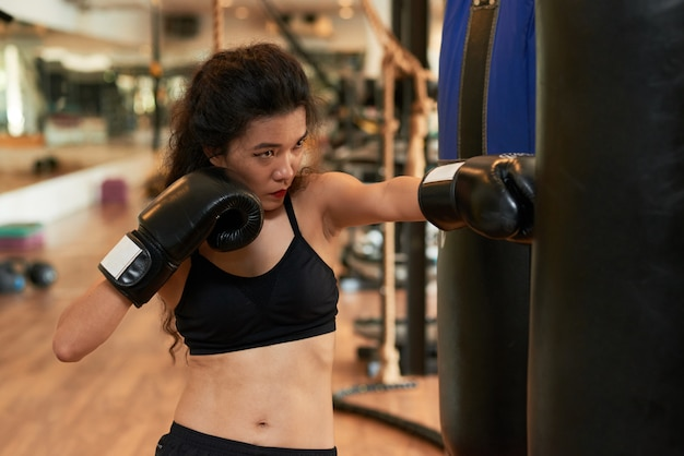 Muay thai female boxer training with punching ball