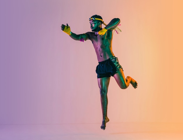 Muay thai. young man exercising thai boxing on gradient background in neon light. fighter practicing, training in martial arts in action, motion. healthy lifestyle, sport, asian culture concept.