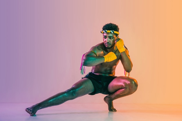 Muay thai. young man exercising thai boxing on gradient background in neon light.