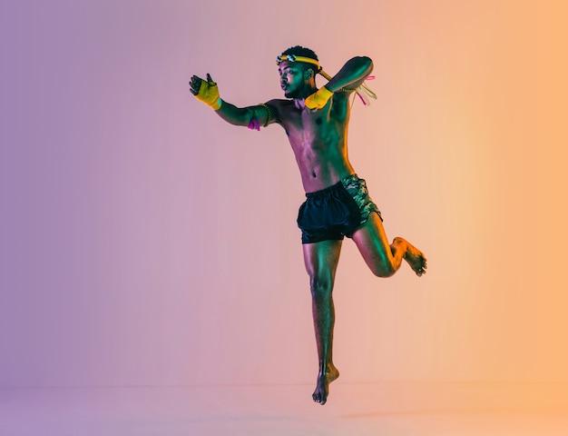 무에타이. 네온 불빛에 그라데이션 배경에 타이어 권투를 운동하는 젊은 남자. 전투기 연습, 무술 훈련, 동작. 건강한 라이프 스타일, 스포츠, 아시아 문화 개념.