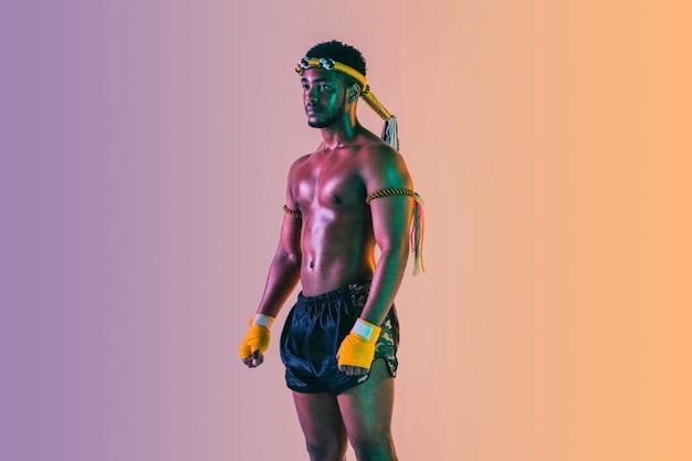 ムエタイ。ネオンの光のグラデーションの背景にタイボクシングを行使する若い男。